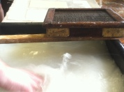European papermaking. Hogging the vat (i.e. agitating the fiber and water to evenly distribute the fibers).